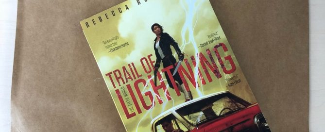"Paperback copy of ""Trail of Lightning"" sitting on top of a very, very large brown envelope."