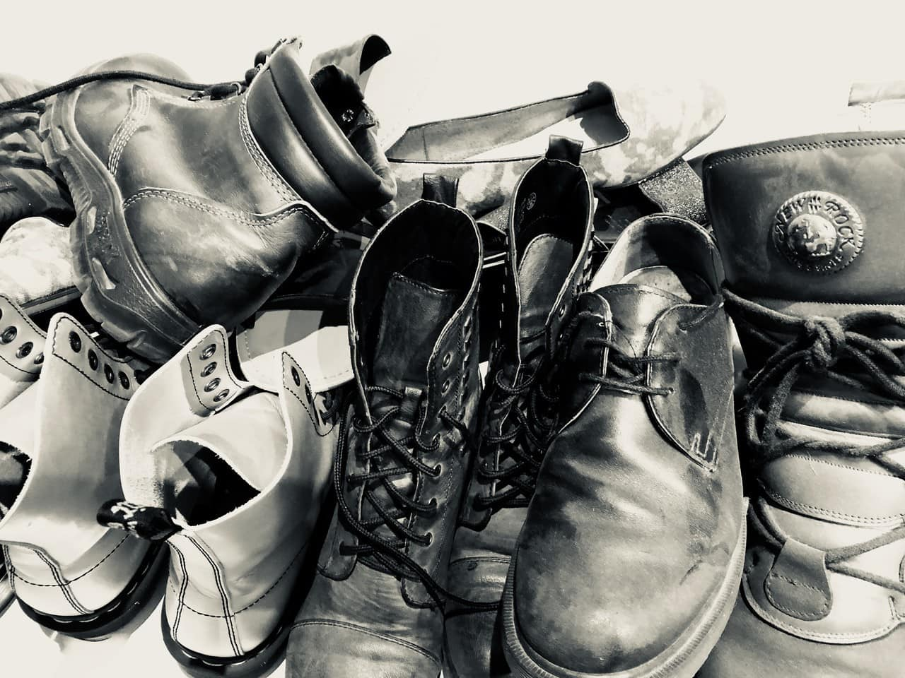 Pile of shoes, mostly boots. Black and white photograph.
