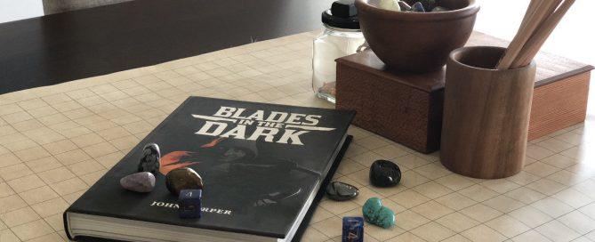 Tabletop RPG accessories and the BLADES IN THE DARK core rulebook.