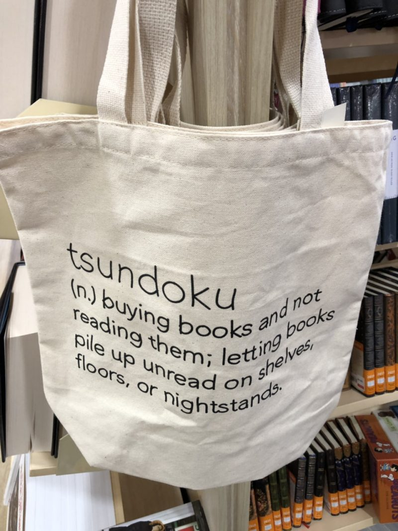 "Canvas book bag with a printed definition of tsundoku; ""buying books and not reading them; letting books pile up unread on shelves, floors, or nightstands."""