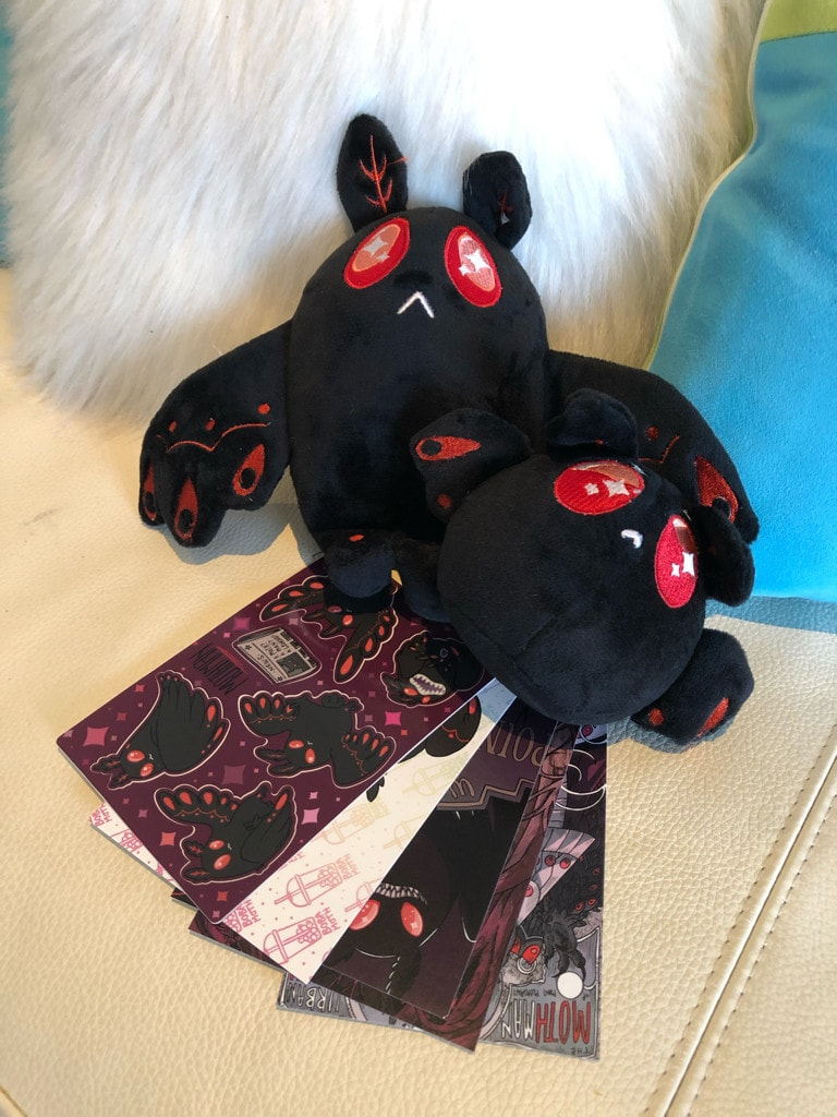 Two mothmen plushies, plus some assorted merchandise.
