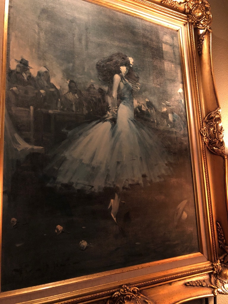 Greyscale, gilt-framed painting of a woman dancing in a tulle dress. Photograph.