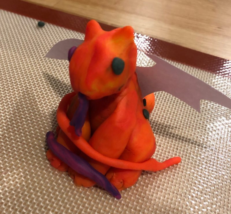 Bright orange Play-Doh dragon with white paper cut-out wings.