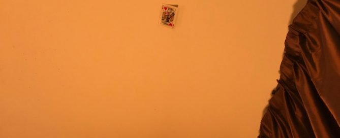 A King of HEarts playing card stuck to a ceiling.