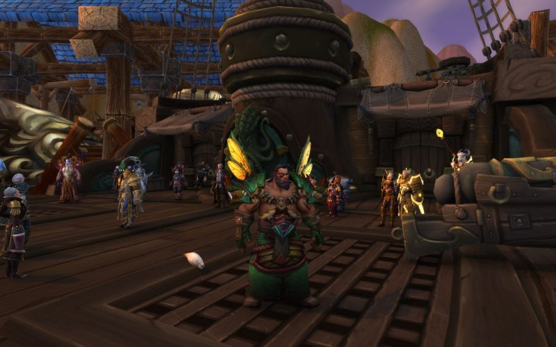 A male Kul Tirian Druid player character, standing on the deck of a ship. A variety of Alliance leaders can be seen in the background.