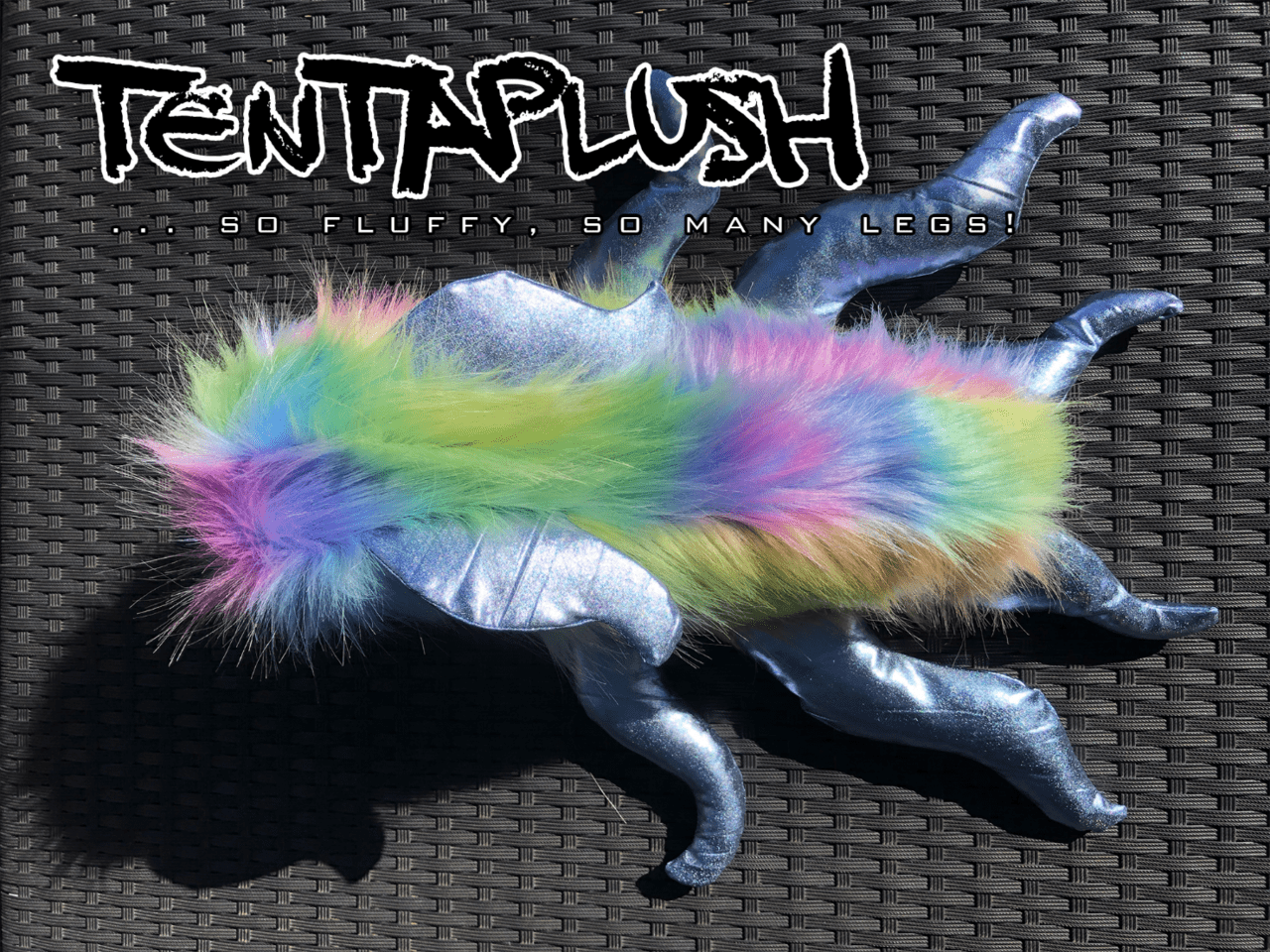 Top-down view of a plush toy. The guinea-pig like body is done in pastel rainbow fur, with six silver lame tentacles protruding from the body.