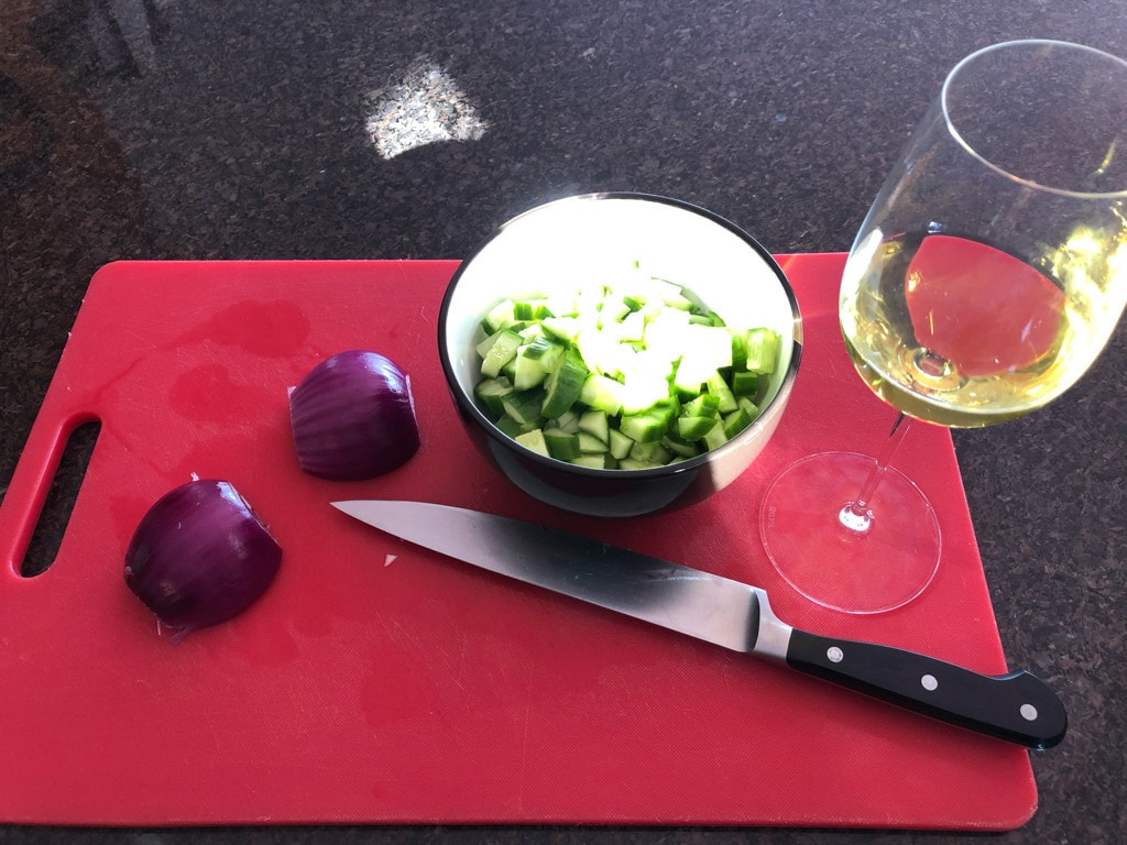 A red chopping board with a bowl of diced cucumber, a cut red onion, a knife, and a glass of white wine.