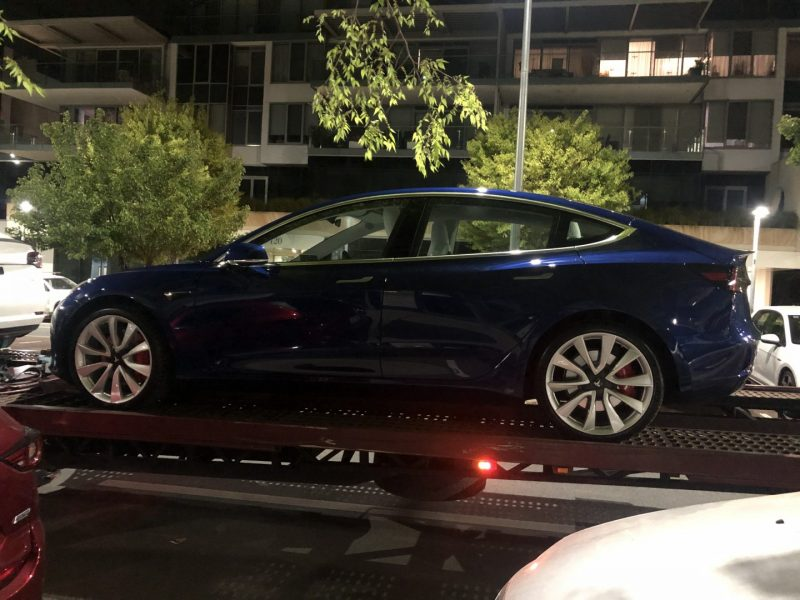 Blue Tesla Model 3 sitting on a delivery truck at night.