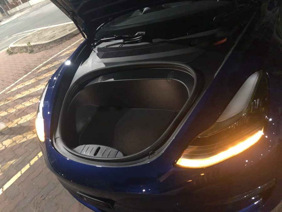 Blue Tesla with an open bonnet, showing an empty storage space where an engine would normally be.