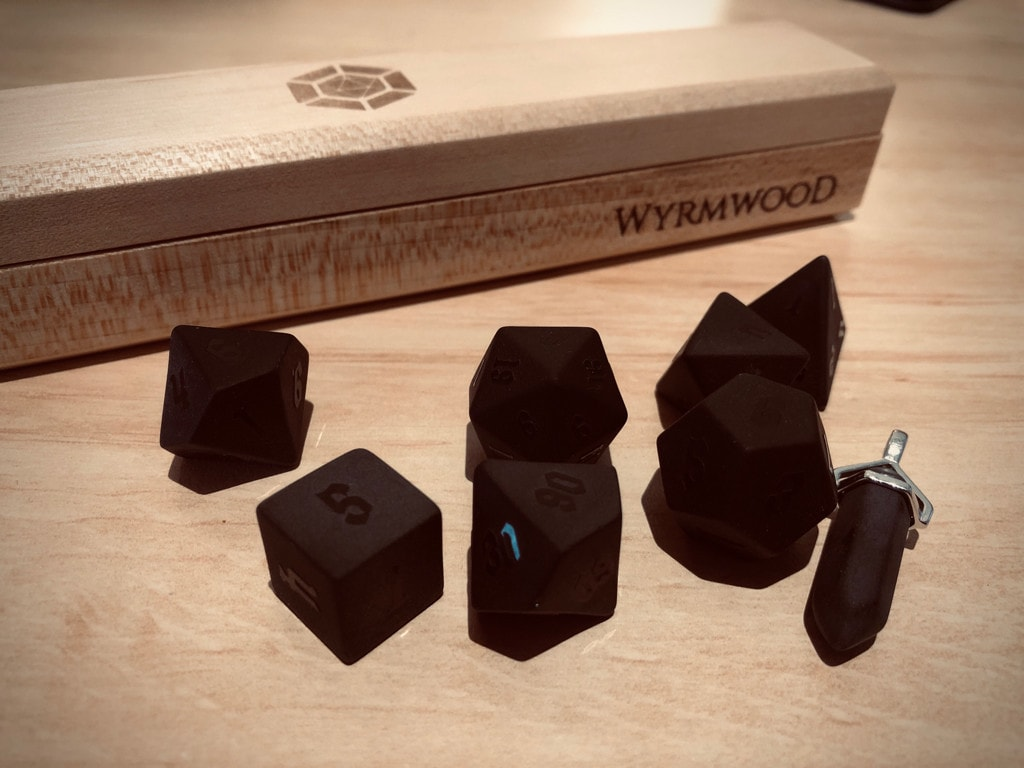 A set of matte black stone dice with wooden carry box in the background.