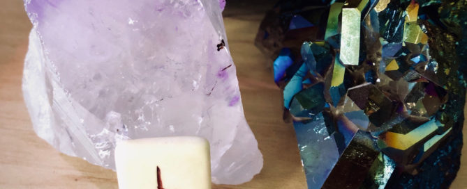 Thurs rune propped up in front of two crystals.