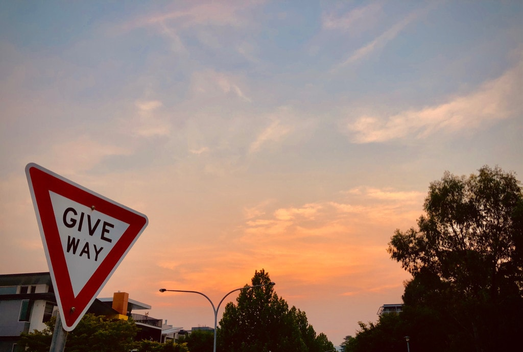 Blue and peach sunset behind a GIVE WAY roadsign.