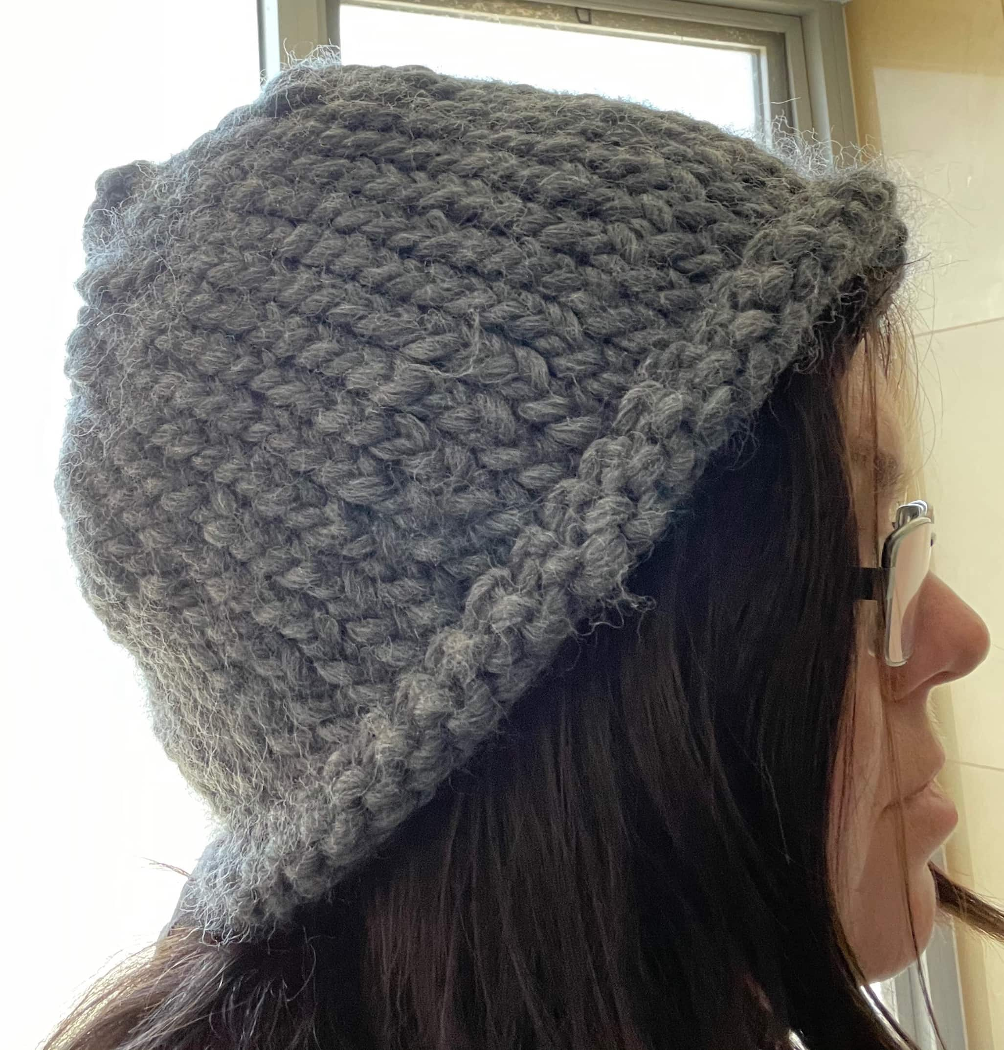 Profile of me in a chunky knit grey beanie.